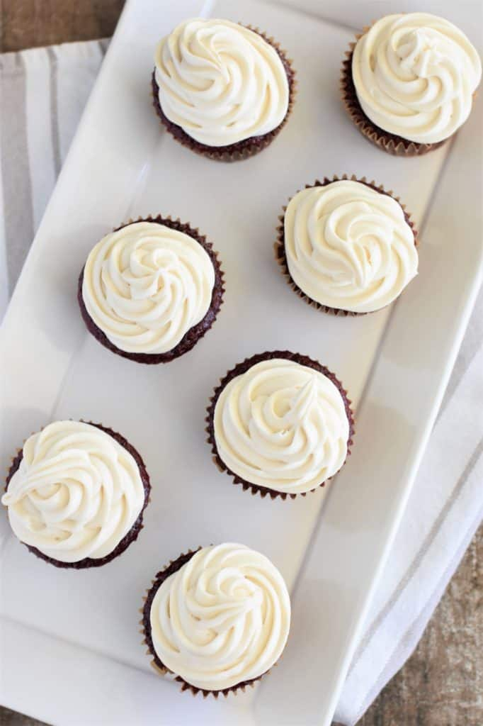 overhead of red velvet cupcakes with frosting on a white serving tray