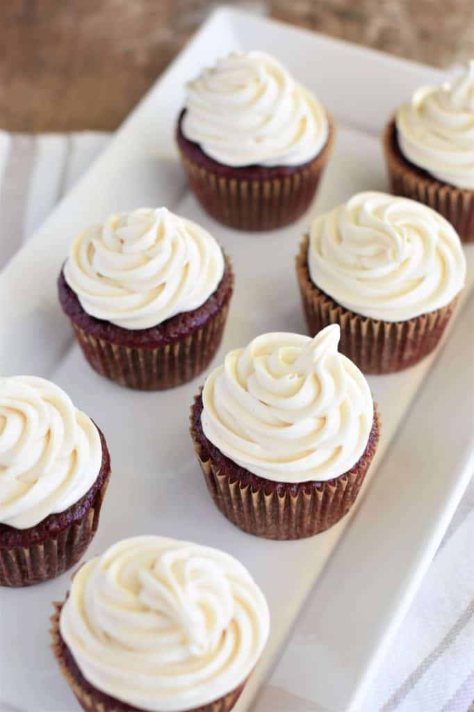 cupcakes with frosting on a white serving plate