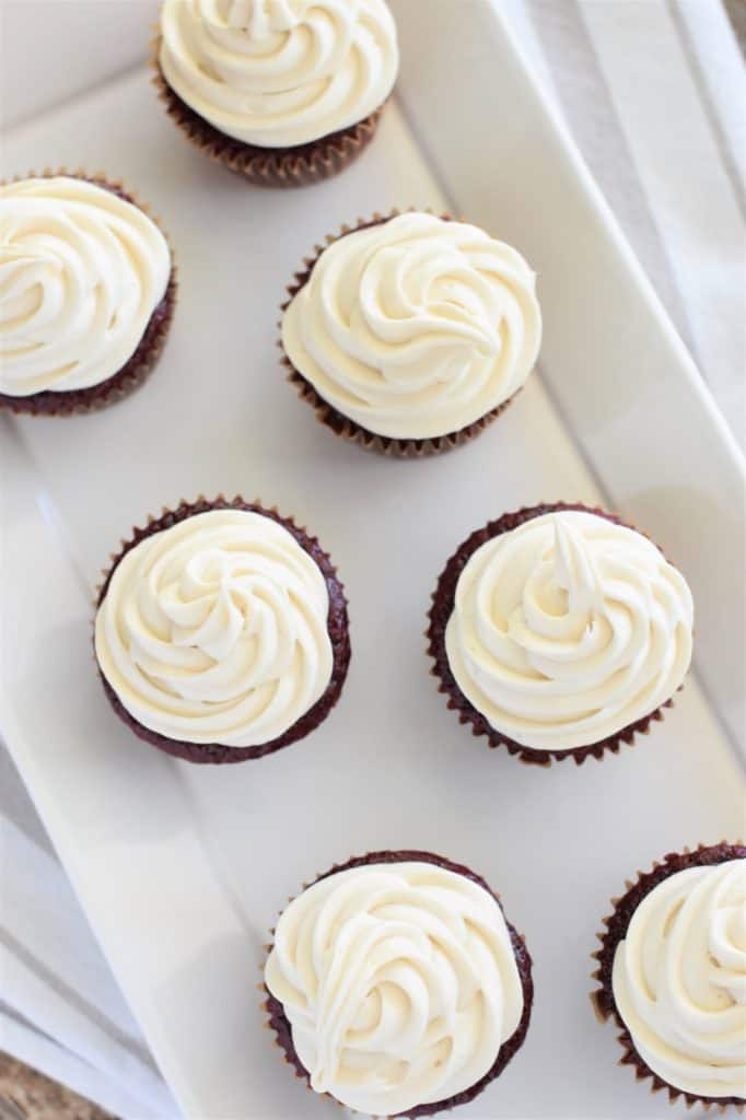 overhead of cupcakes with frosting on white serving tray