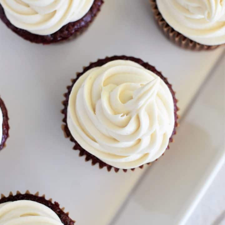 close-up overhead of frosting on a cupcake with parts of others in view