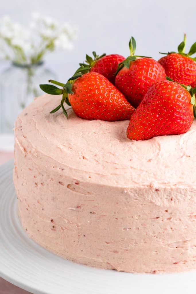 close-up of left side of cake on white cake stand with strawberries on top