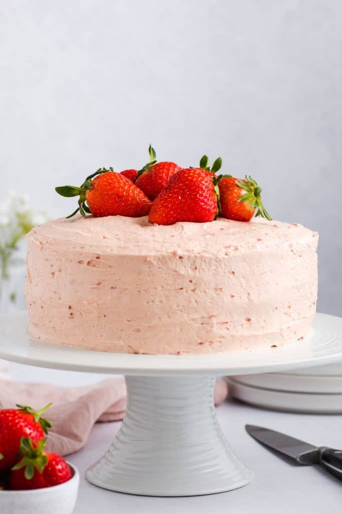 front view of cake on a white cake stand topped with fresh strawberries