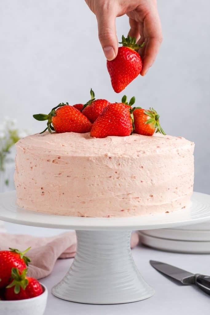 hand placing a strawberry on top of the cake