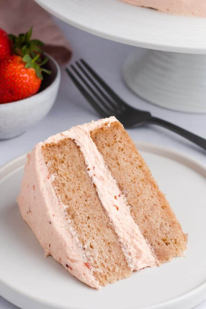 close-up of slice of cake on a white plate with fork behind it