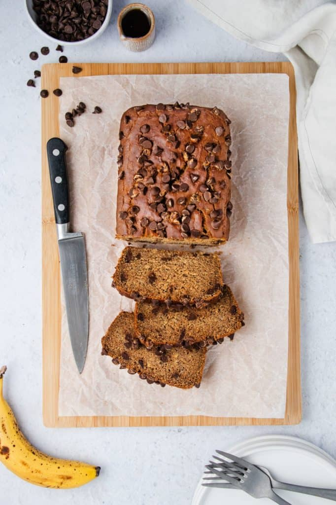 overhead of loaf of buckwheat banana bread on parchment paper on a wooden board with three slices cut