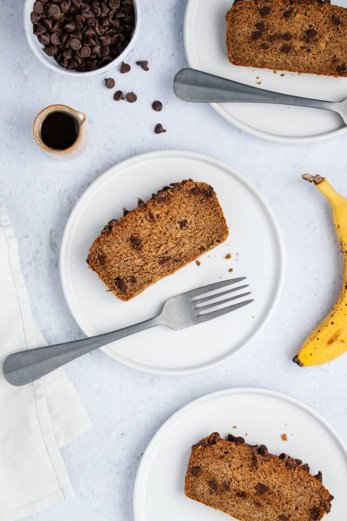 overhead of slices of banana bread on white plates with forks