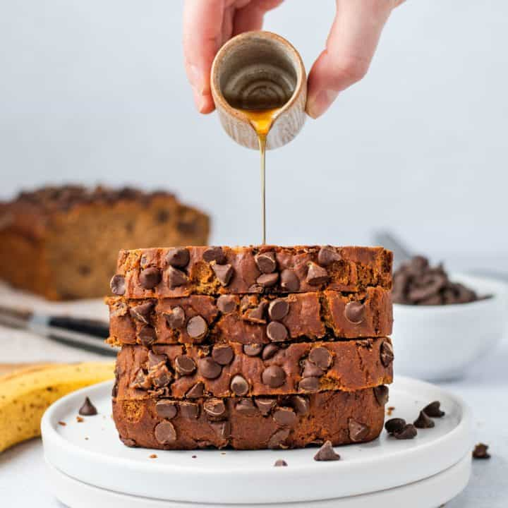 pouring maple syrup on a stack of banana bread slices