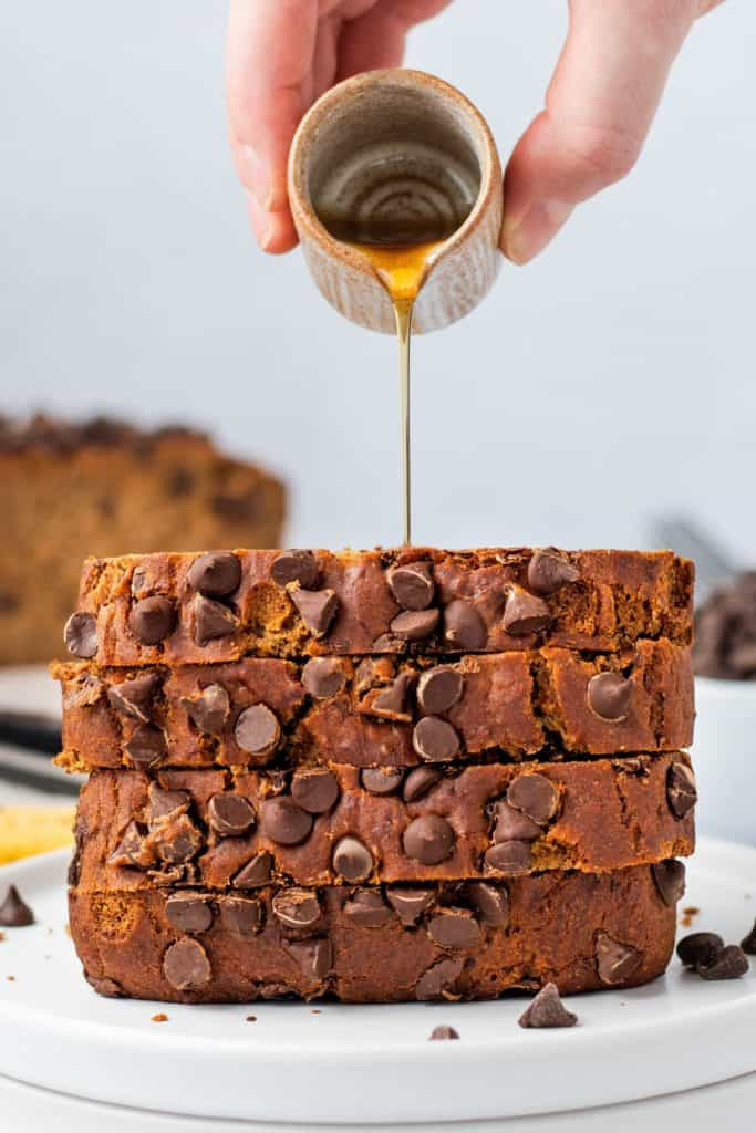 close-up of maple syrup being poured onto a stack of banana bread slices on a white plate