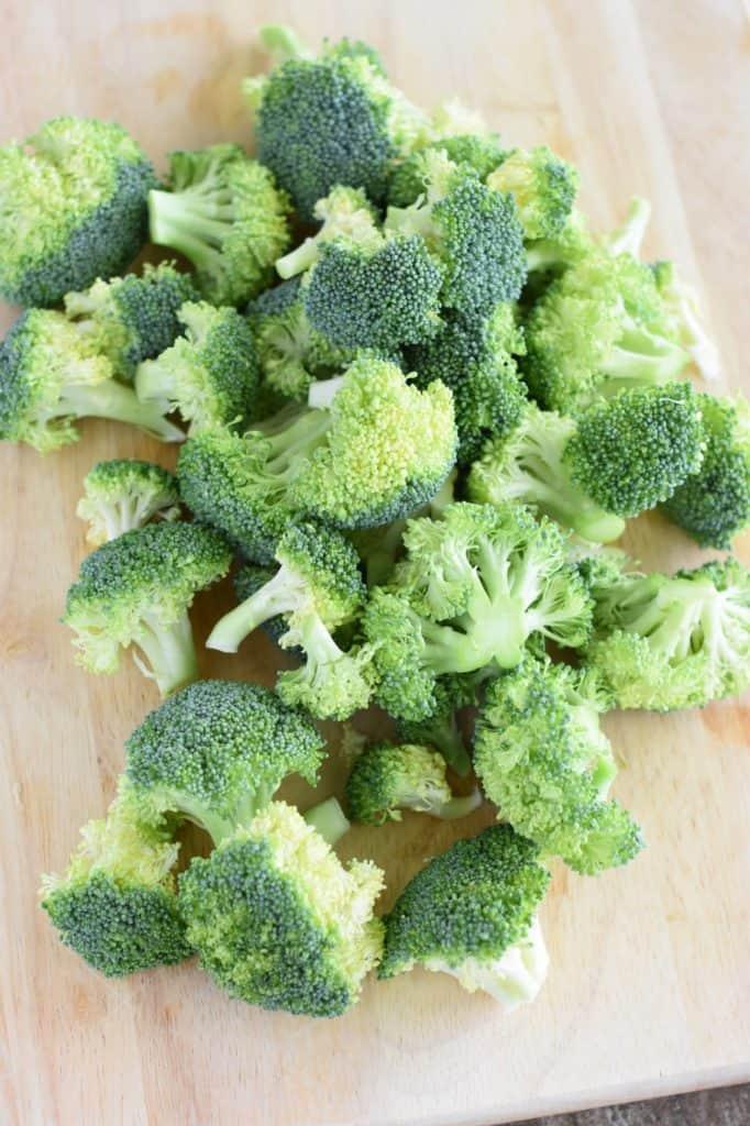 broccoli florets on a wooden cutting board
