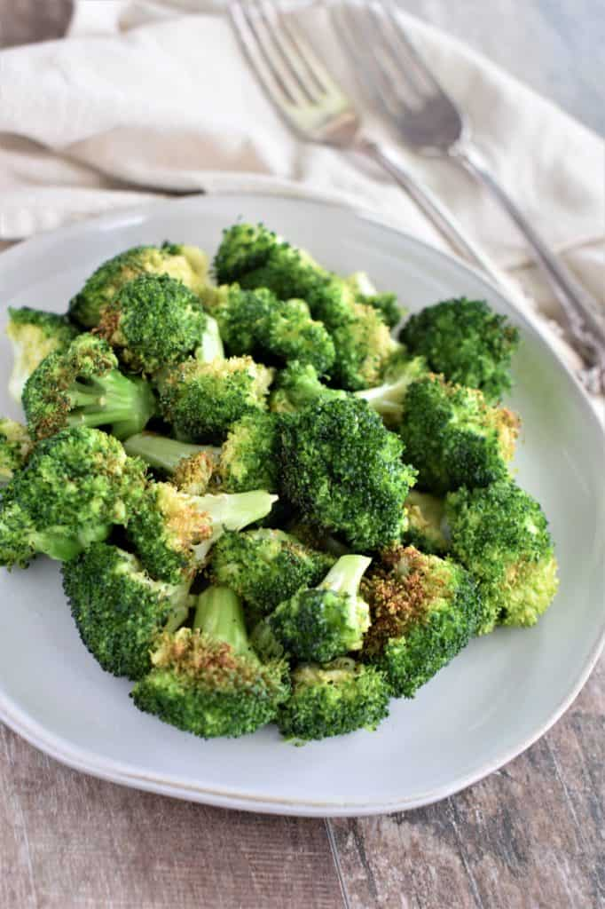 overhead of broccoli in a white plate after cooking with two forks blurred out toward top right