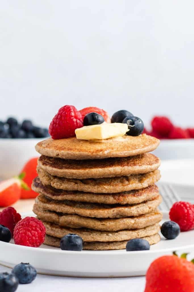 stack of 8 pancakes on a white serving dish with vegan butter, maple syrup and fresh fruit