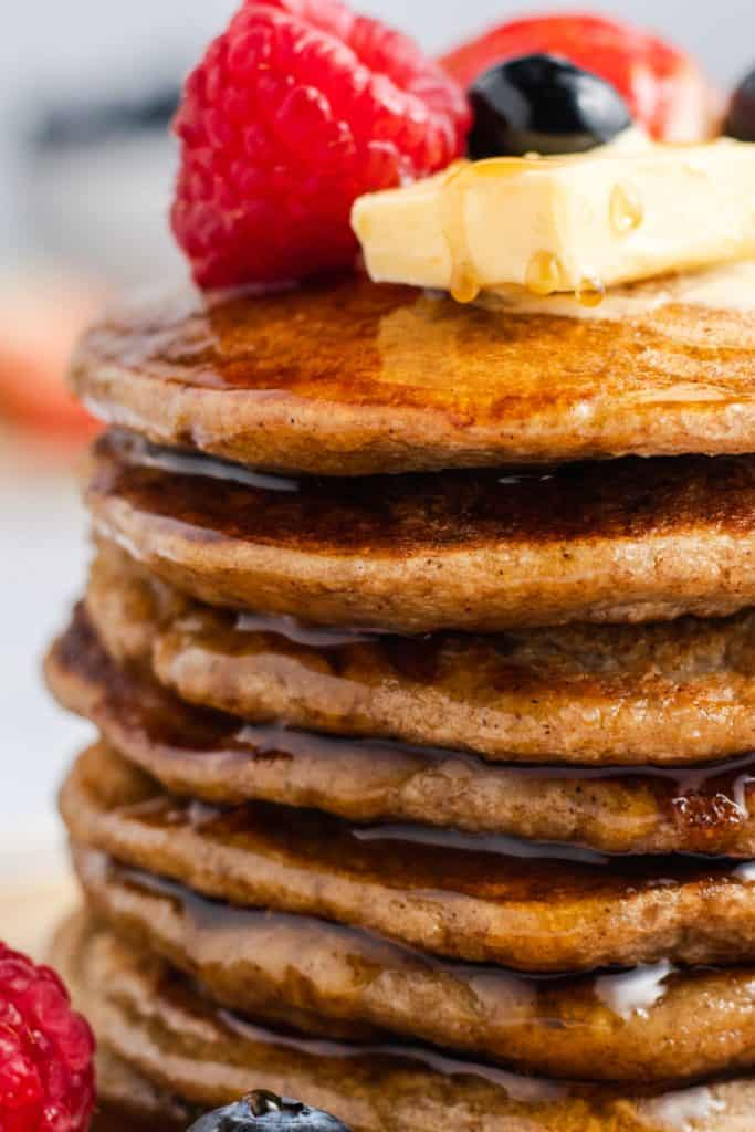 close-up side view of stack of vegan banana oat pancakes dripping with maple syrup