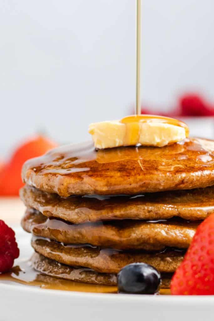 close-up of maple syrup drizzling onto stack of pancakes