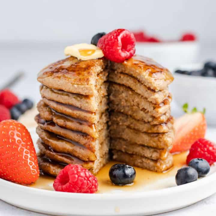 stack of pancakes with middle piece cut out and topped with vegan butter, maple syrup and fresh fruit
