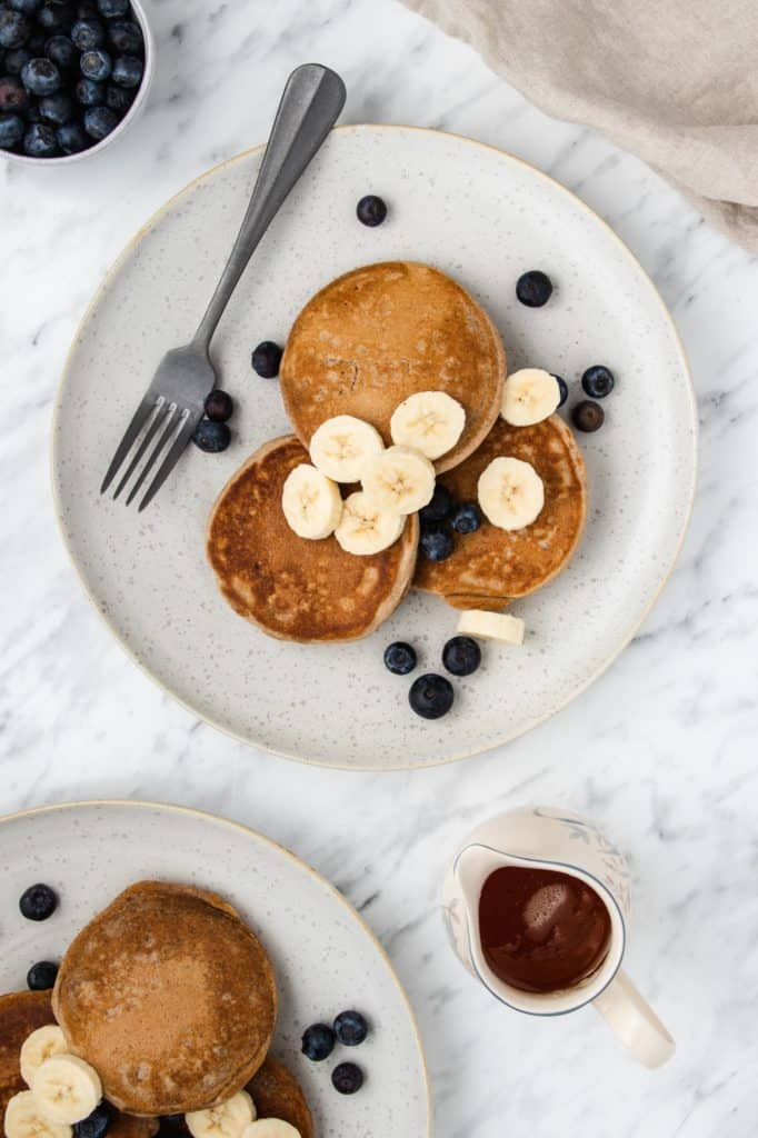 overhead of three pancakes on a plate with bananas and blueberries and part of another plate of pancakes in view on bottom left