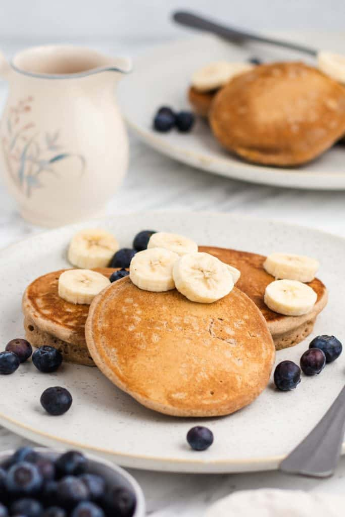 front view of pancakes on a plate with bananas and blueberries
