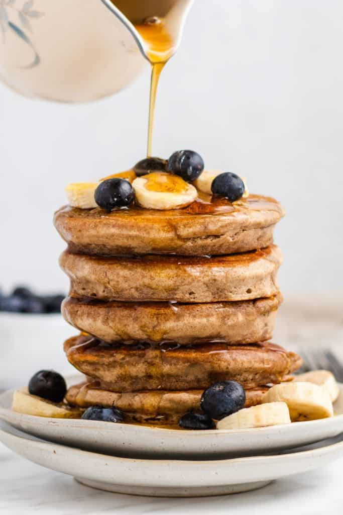 pouring maple syrup onto a stack of vegan buckwheat pancakes on two plates with bananas and blueberries