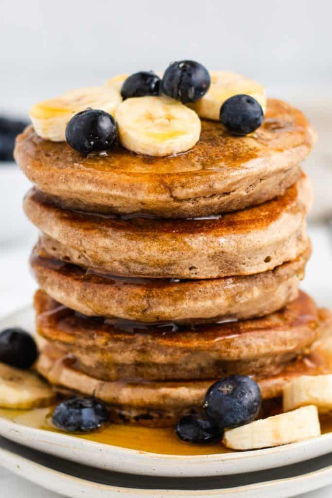 front view of pancakes stacked up with maple syrup, bananas and blueberries