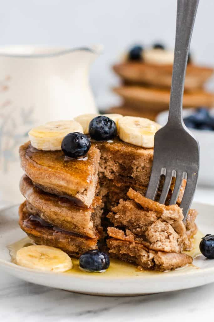 """fork in part of pancake """"cut"""" out of the stack on a plate with maple syrup, bananas and blueberries"""
