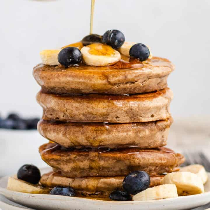 close-up front view of syrup pouring onto stack of pancakes with bananas and blueberries