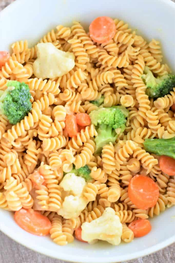 pasta mixed with sauce and veggies in mixing bowl and ready to serve
