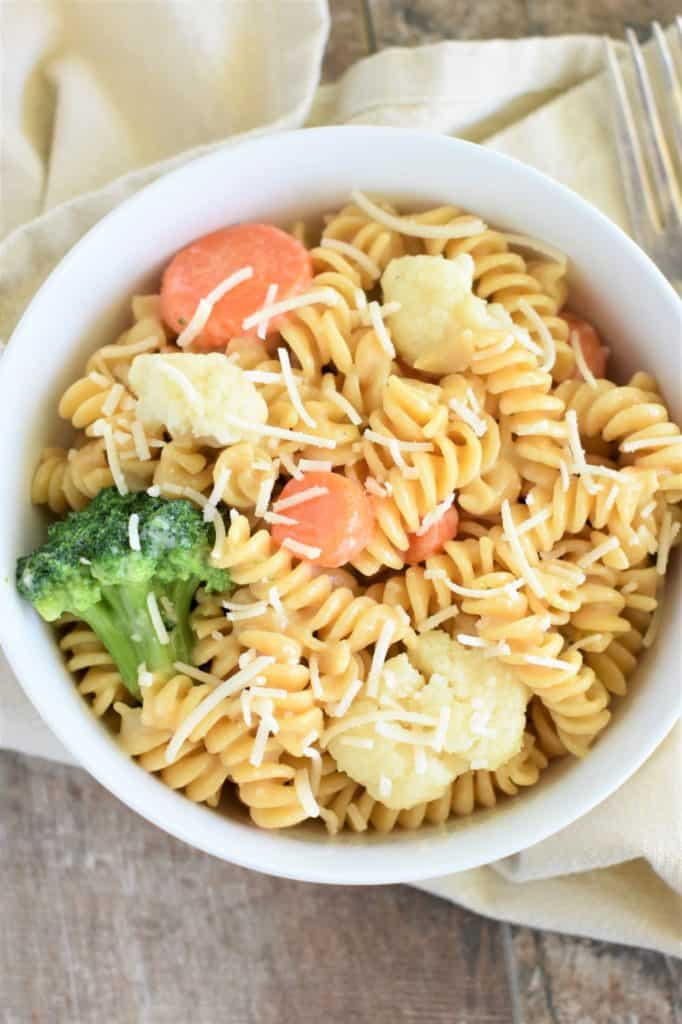 overhead of pasta primavera in a white bowl garnished with vegan Parmesan