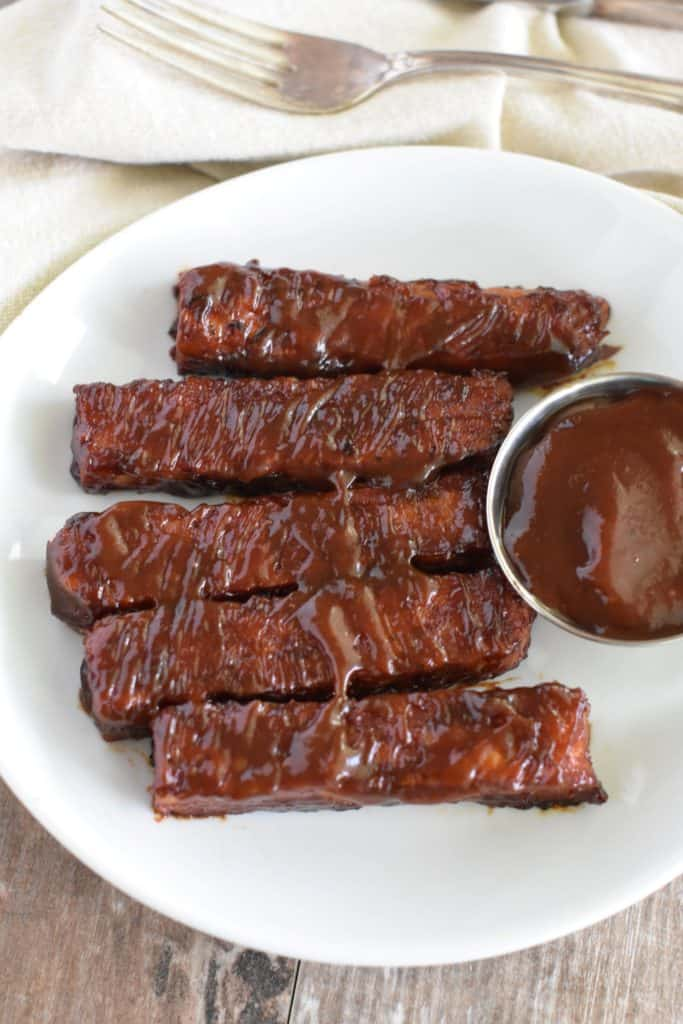 overhead of BBQ tempeh ribs on a white plate with cup of barbecue sauce
