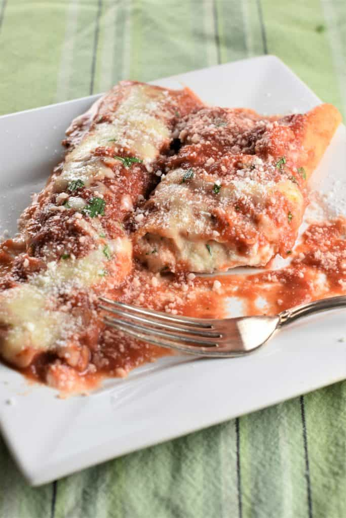 one and a half manicotti on a white plate with a fork