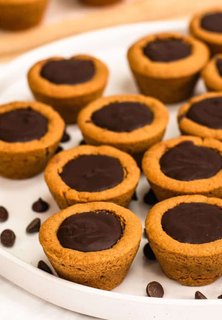 cookie cups on a white serving dish with some chocolate chips around