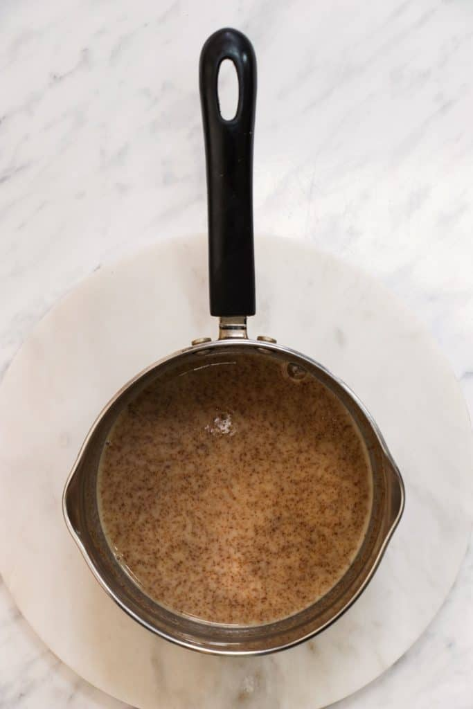 almond milk, almond butter and maple syrup after being heated in the saucepan