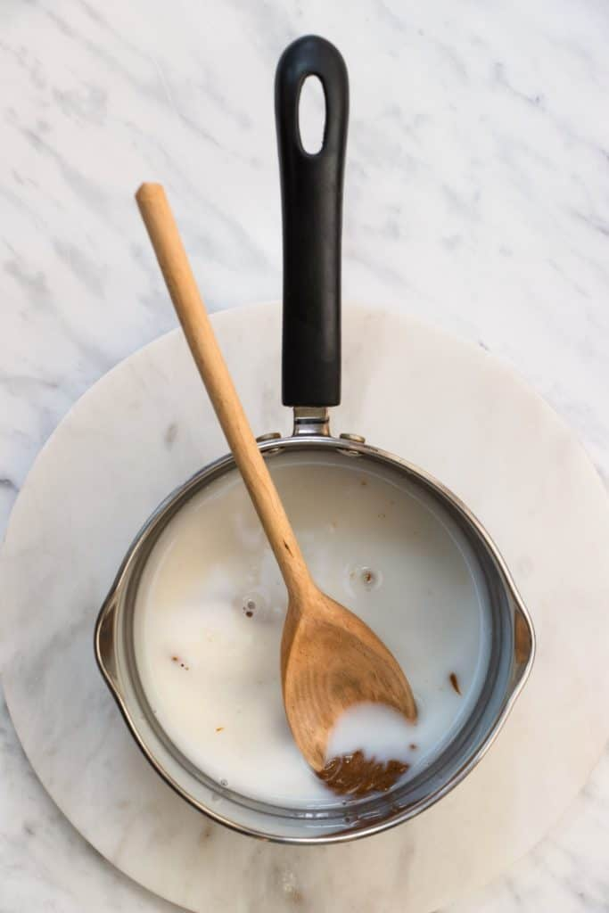 almond milk, almond butter and maple syrup in a saucepan with a wooden spoon in it