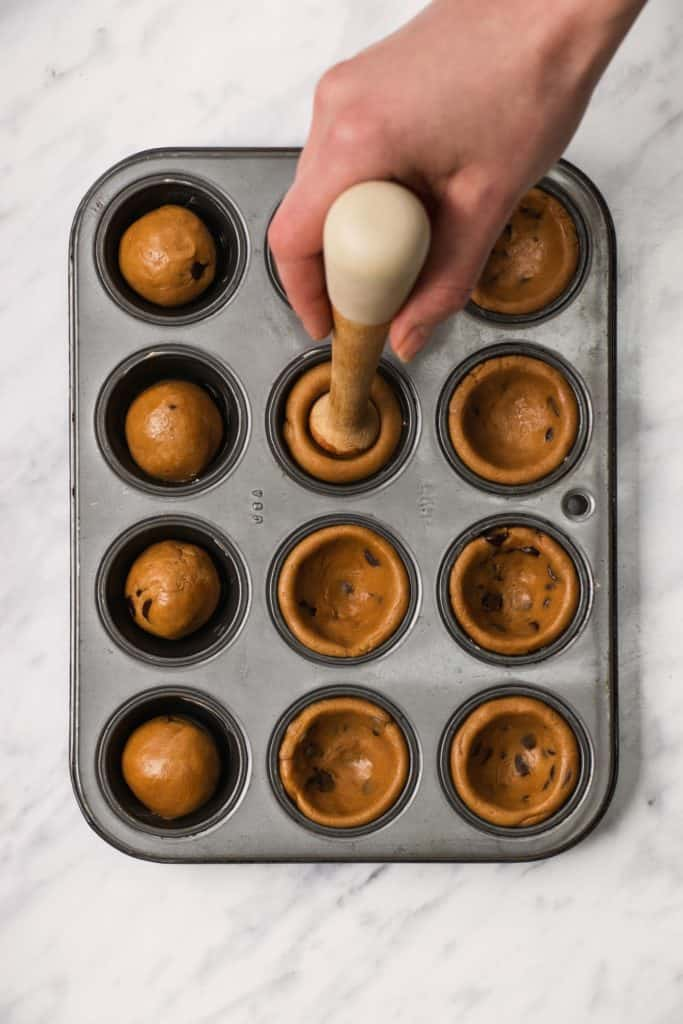 pressing down on dough balls in mini muffin tin