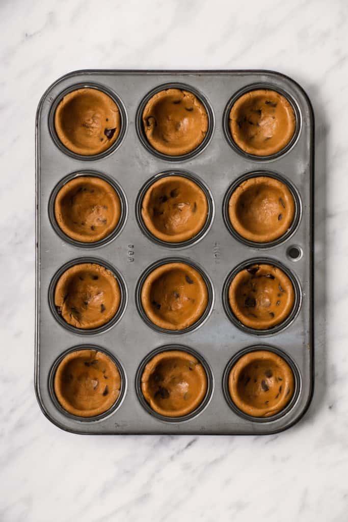 dough in mini muffin tin after pressing