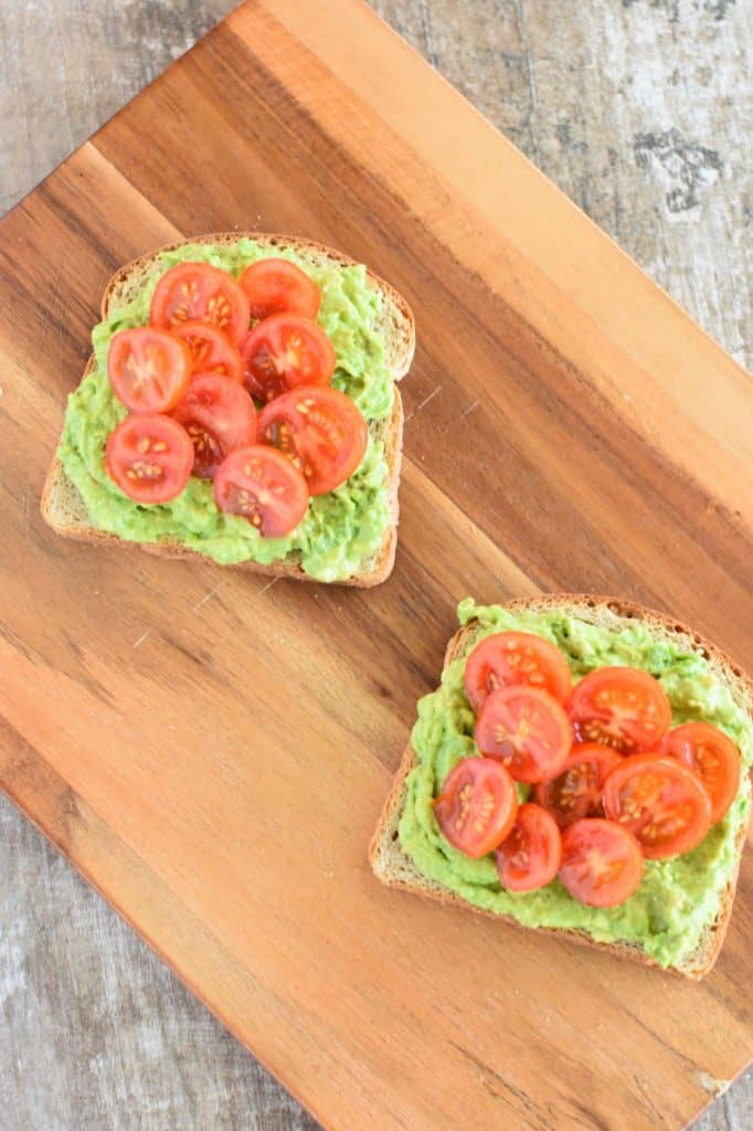 two slices of toast on wooden board with mashed avocado and tomatoes
