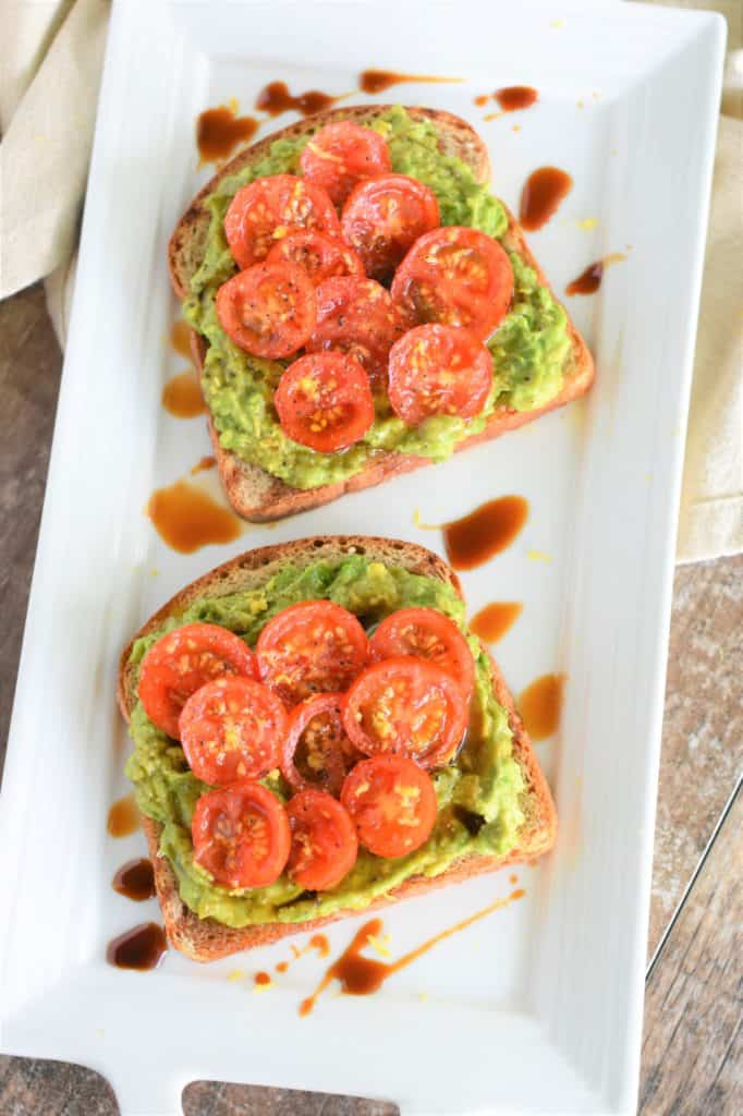 overhead of two slices of tomato avocado toast on white serving dish