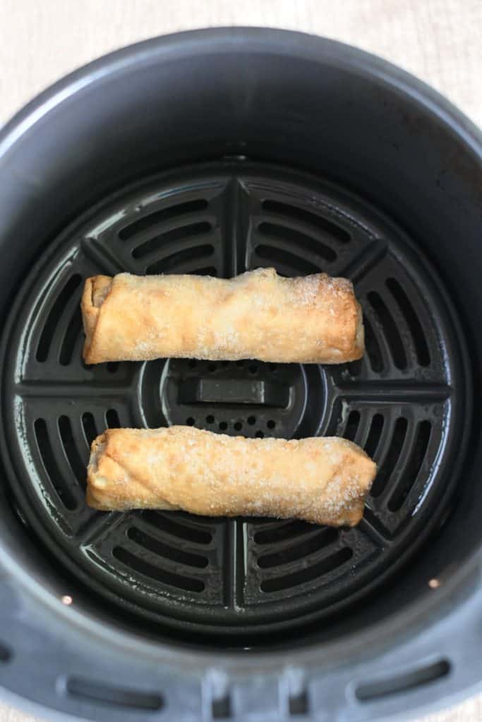 frozen egg rolls in air fryer basket before cooking