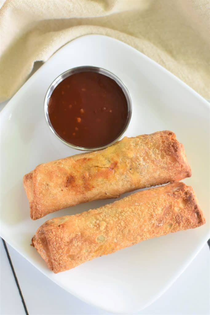 overhead of two egg rolls on a white plate with sweet chili sauce on the side