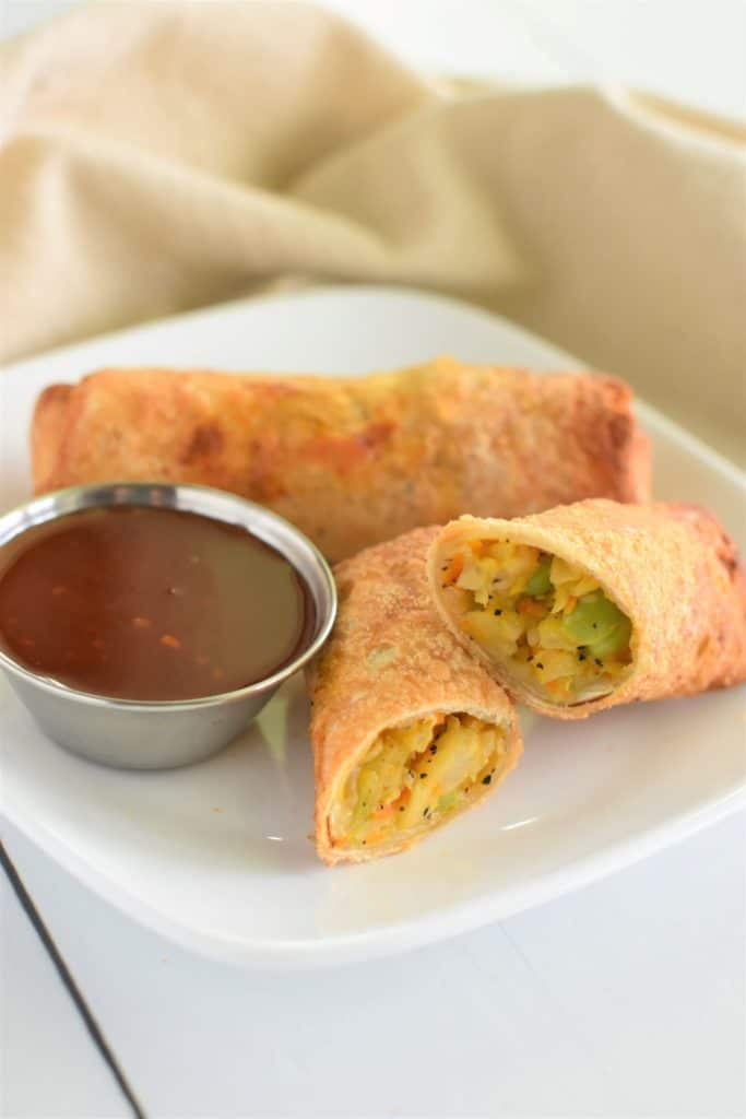 open egg roll on a plate with a closed one behind it and dipping sauce on the left of the open one