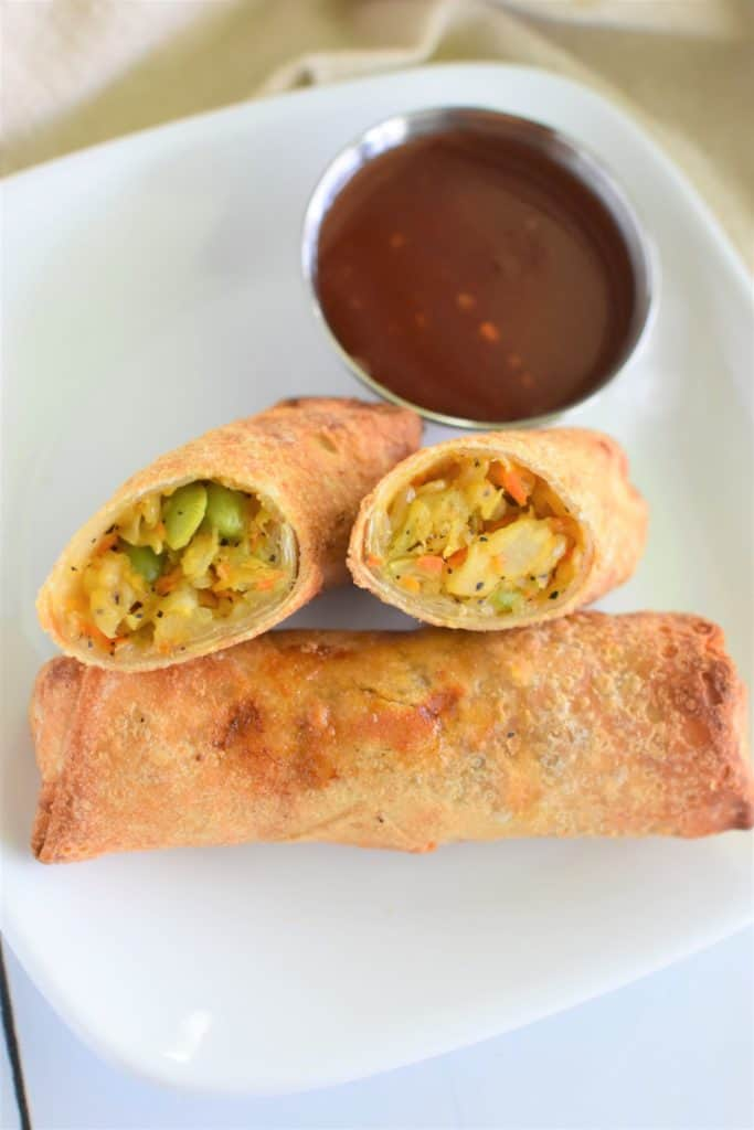 two open halves of egg roll facing up leaning on an unopened egg roll with dipping sauce on a white plate