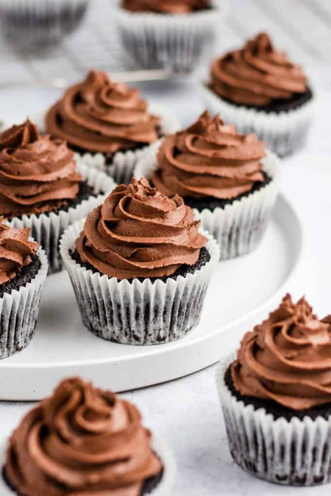 vegan chocolate cupcakes on a white plate with others around it