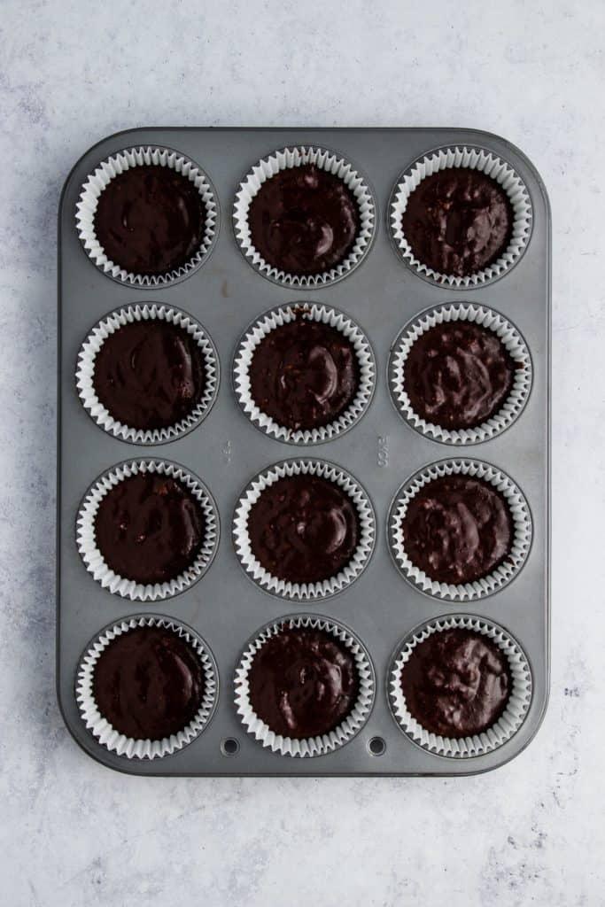 cupcake batter in baking cups in muffin tin
