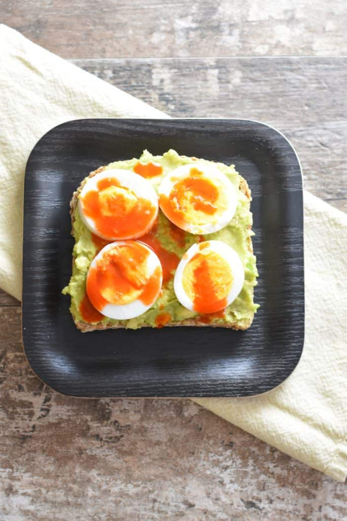 overhead of slice of avocado toast with boiled eggs and hot sauce