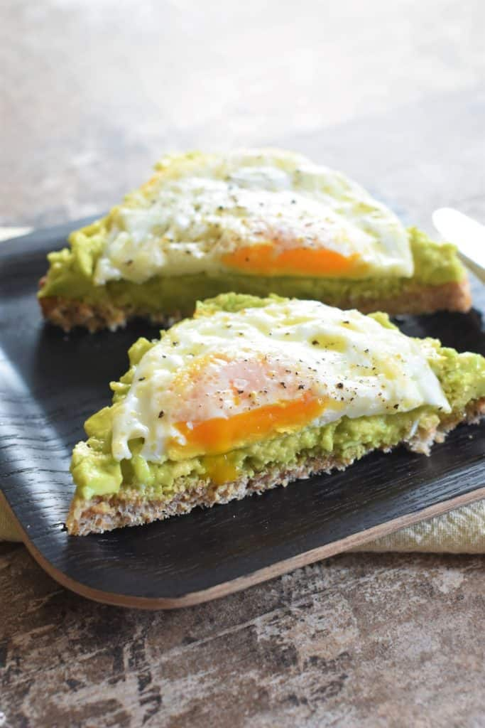 front view of cut piece of avocado toast with fried egg