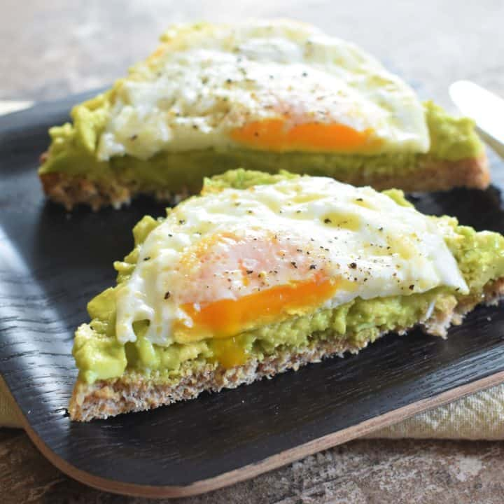 close-up of cut slice of avocado toast with fried egg
