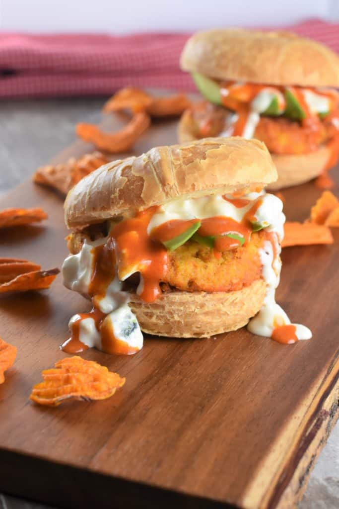 burger with avocado, Buffalo sauce and blue cheese dressing on wooden board with sweet potato chips around and another one in the background