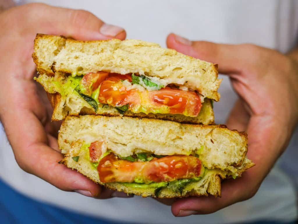 vegan tomato mozzarella sandwich with pesto being held