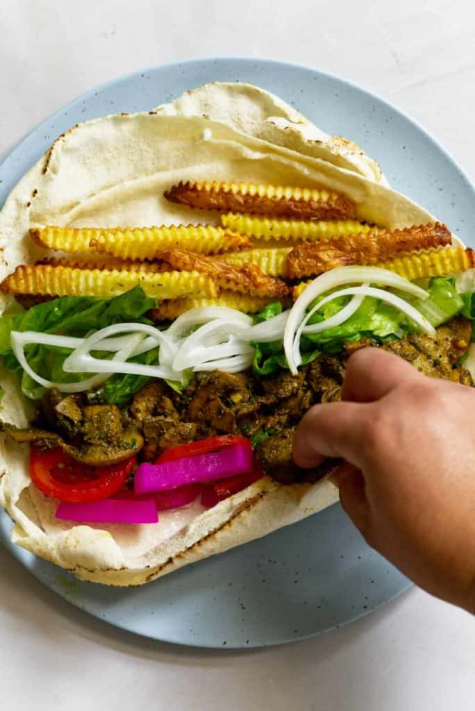 hand getting ready to roll up vegan Shawarma wrap on a plate