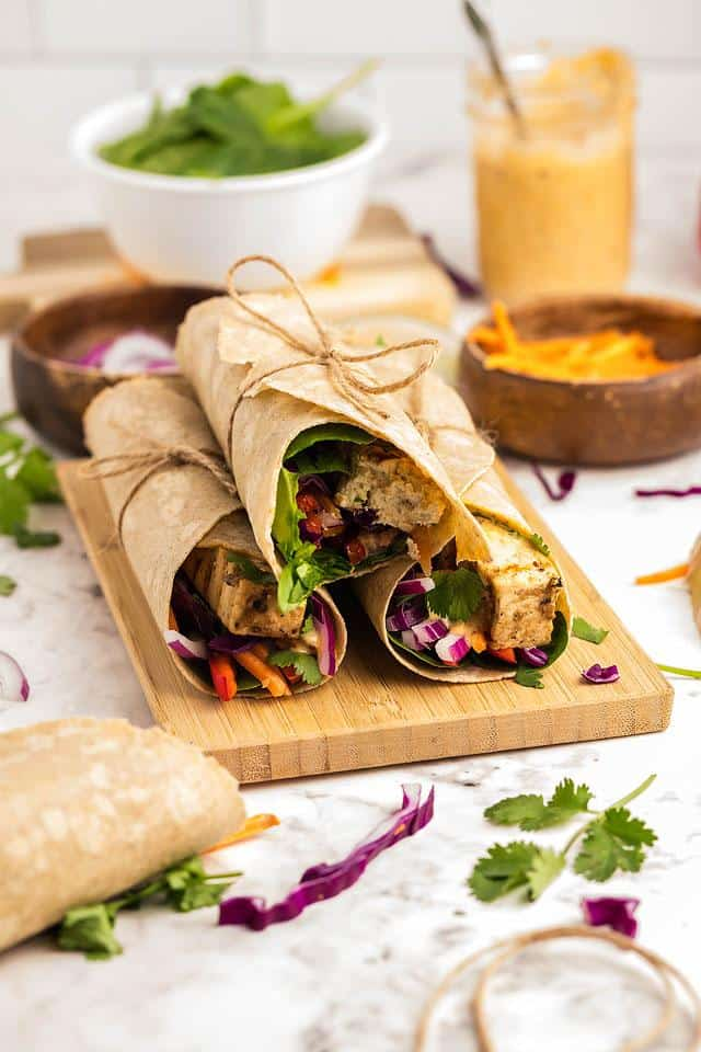 tofu thai wraps on wooden board with ingredients around