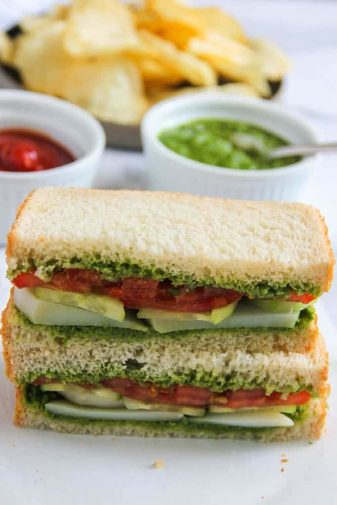 Bombay sandwich on white surface, halves stacked on top of each other with chips and dips in the background