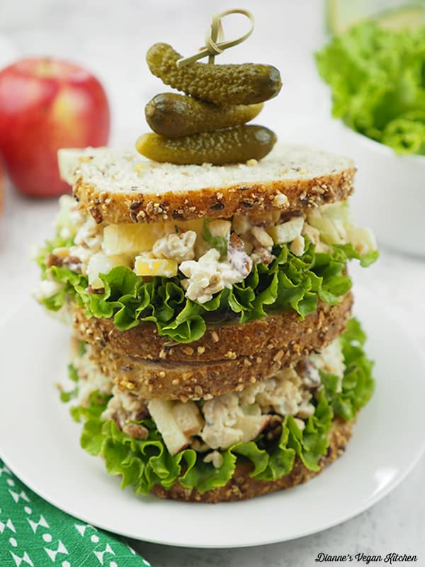 apple pecan tempeh sandwiches on top of each other with pickles garnished on top